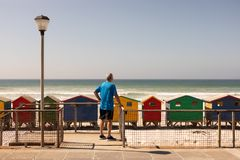Rear view of senior man standing near railing at beach. With ocean in the background royalty free stock photography