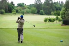 Man teeing off on a golf course with a driver. Rear view of a senior man teeing off on a golf course with a driver royalty free stock images
