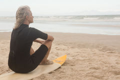 Rear view of senior woman sitting on surfboard Royalty Free Stock Photos
