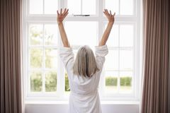 Rear View Of Senior Woman Stretching In Front Of Bedroom Window stock image