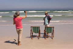Senior woman clicking photo of senior man on beach. Rear view of senior women clicking photo of senior men on beach in the sunshine stock images