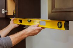 Rear view of serviceman fixing cabinet kitchen. Rear view of serviceman fixing cabinet with in kitchen Stock Photography