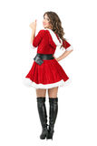 Rear view of sexy female Santa Claus showing thumbs up turning to camera Stock Images