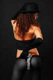 Rear view of sexy gangster hiding a handgun. Pretty woman is hiding a handgun behind her back on the dark background. Sexy gangster is wearing tight trousers, a Stock Photography