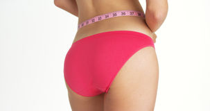 Rear view of sexy woman measuring waist. With pink underwear Royalty Free Stock Photo