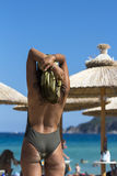 Rear View of Sexy Woman Standing on Beach. Rear view of a young woman wearing swimsuit and silk scarf , standing at the beach and looking out at blue sea Stock Photography