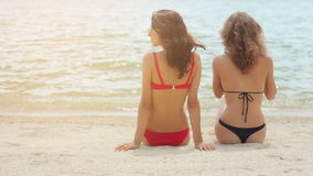 Rear view of sexy women in swimsuit sitting on sandy beach. Rear view of sexy young women in swimsuit sitting on sandy beach in slow motion stock footage