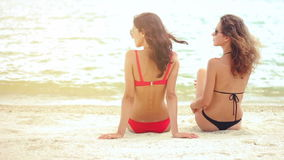 Rear view of sexy women in swimsuit sitting on sandy beach. Rear view of sexy young women in swimsuit sitting on sandy beach in slow motion stock video