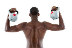 Rear view of shirtless fit man lifting kettle bells Stock Photo