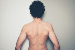 Rear view of shirtless man against dual colored background Royalty Free Stock Photos