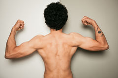 Rear view of shirtless man against dual colored background Stock Images