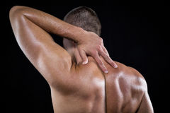 Rear view of shirtless man with neck pain Stock Photos
