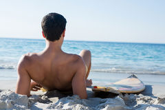 Rear view of shirtless man reclining by surfboard at beach. Rear view of shirtless man reclining by surfboard on sand at beach during sunny day Stock Photography