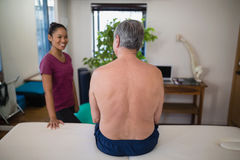 Rear view of shirtless senior male patient sitting on bed looking at smiling female therapist. In hospital ward Stock Photos