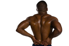 Rear view of shirtless sportsman suffering from back pain. While standing against white background Stock Photo