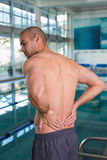 Rear view of shirtless swimmer with back ache by pool Stock Image