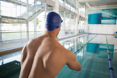 Rear view of shirtless swimmer by pool at leisure center Stock Photos