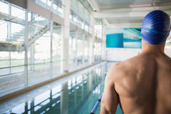 Rear view of shirtless swimmer by pool at leisure center Royalty Free Stock Photo