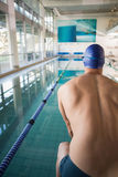 Rear view of shirtless swimmer by pool at leisure center Stock Photography
