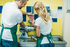Rear view of shop assistants working with fresh raw meat. In supermarket royalty free stock images