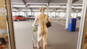 Rear view shot of beautiful young woman walking out of supermarket with trolley full of products stock video