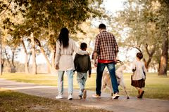 Rear view shot of family with two children. Walking the dog in autumn park royalty free stock image