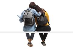 Rear view shot of teen students seated together in an embrace. On white background Stock Images