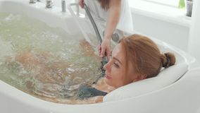 Rear view shot of a woman enjoying hydromassage in whirl pool bath stock video