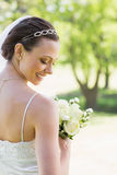 Rear view of shy bride with flowers in garden Stock Photography