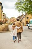 Rear view of a silhouette of a loving couple, hugging while visiting a destination city, walking along the old street of English royalty free stock photo
