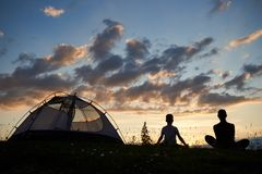 Rear view of silhouette of woman and boy sitting on grass with wild flowers relaxing near the campsite at sunset. Rear view of a silhouette of woman and boy Royalty Free Stock Photos
