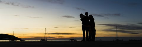 Rear view of silhouetted family outdoors  hugging looking at the. Sunset with the sea, mountain and sailboats behind in a wide panoramic view against evening Stock Image