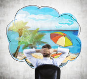 Rear view of sitting businessman who dreams about vacation on the beach. Royalty Free Stock Photography