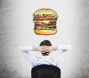 A rear view of sitting relaxing man who is dreaming about burger. A fast food concept. Stock Image