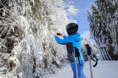 Rear view of skier taking picture with her cell phone Stock Image