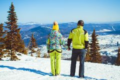 Couple is standing in the mountains in winter. Rear view of skiers on ski slope with mountains in background. Horizontal shot Royalty Free Stock Photography