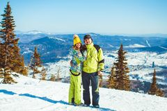 Couple is standing in the mountains in winter. Rear view of skiers on ski slope with mountains in background. Horizontal shot Stock Photo