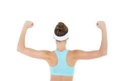 Rear view of slender brunette woman tensing her arm muscles Royalty Free Stock Photo
