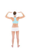 Rear view of slender woman wearing sportswear raising her arms Royalty Free Stock Photography