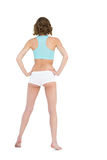 Rear view of slender young woman wearing sportswear posing with hands on hips Stock Photography