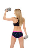Rear view of slim blonde exercising with dumbbells Stock Image