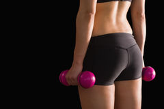 Rear view of slim woman wearing sportswear holding pink dumbbells Stock Images