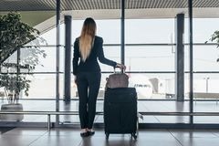 Rear view of slim young female traveler standing in airport terminal holding heavy suitcases looking through the window royalty free stock photo