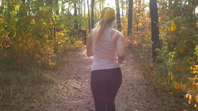 Rear view slow motion shot of young woman with ponytail running at forest