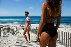 Rear view of a smiling attractive young man is turned back to makes acquaintance with the sexy young woman on the beach. royalty free stock photography
