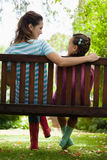 Rear view of smiling woman and girl sitting on bench Stock Photo