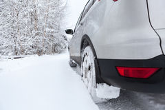 Rear view of snow tires of car driving over snowdrift, winter season Stock Photography
