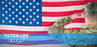Composite image of rear view of soldier saluting. Rear view of soldier saluting against rippled us flag Royalty Free Stock Photo