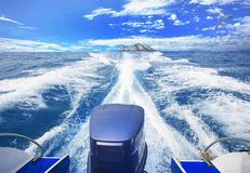 Rear view of speed boat leaving from lonely island Royalty Free Stock Photo