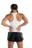Rear view of sportswoman suffering from back pain. While standing against white background Stock Photos